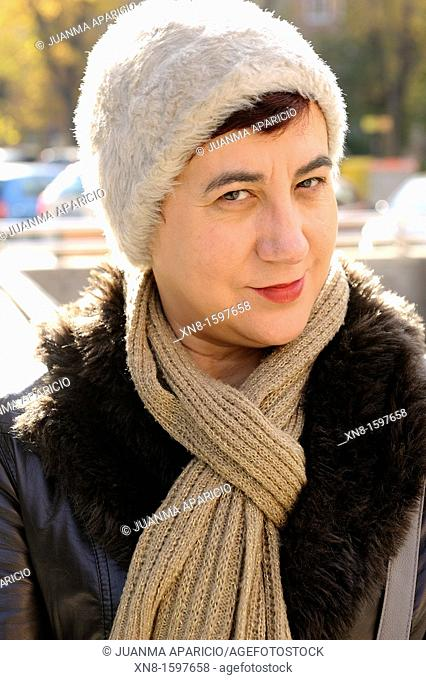 Middle-aged woman with wool cap and scarf looking to the camera sideways