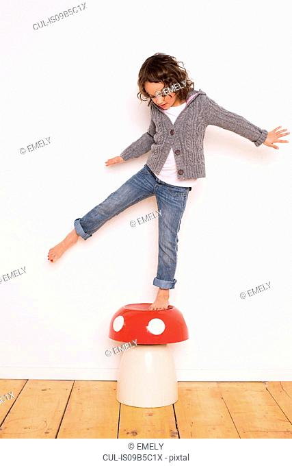 Young girl balancing on toadstool, studio shot