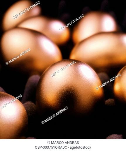many golden eggs on a black surface
