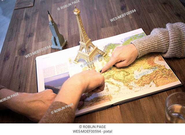 Hands on atlas with model of Eiffel tower and Empire State Building