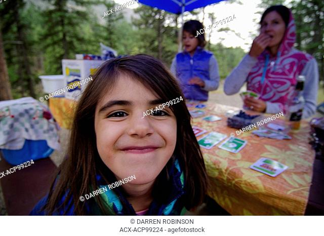Young girl and her family enjoy games while camping at Stemwinder Provincial Park, near Hedley, in the Similkameen region of British Columbia, Canada