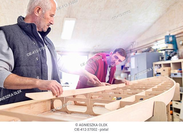 Male carpenters assembling wood boat in workshop