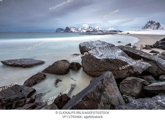 Rocks on the beach partially snow on a cold winter day. Myrland. Lofoten Islands Northern Norway Europe