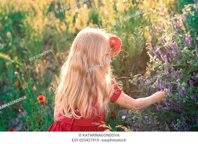 small girl with long blond hair picking flowers rear view