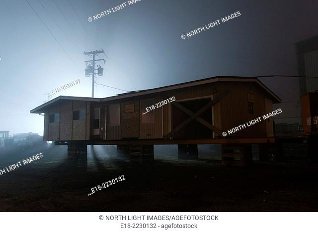 Canada, BC, Delta. residential home up on blocks, in the process of being moved to a new location. Night shot, rear lit by street light