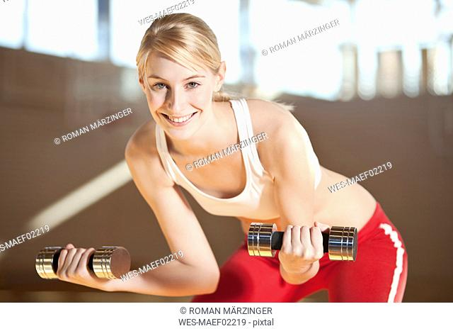 Germany, Mauern, Woman lifting weights, smiling, portrai
