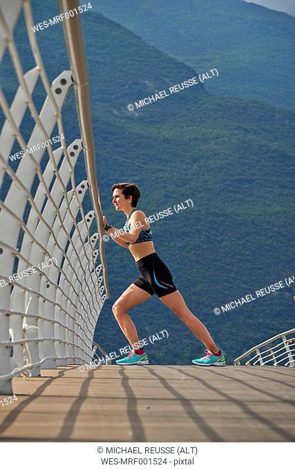 Italy, Trentino, woman stretching on bridge at Lake Garda