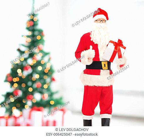 holidays and people concept - man in costume of santa claus with gift box showing thumbs up gesture over living room and christmas tree background