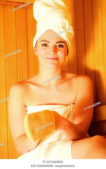 Spa beauty treatment and relaxation concept. Woman white towel relaxing in wooden sauna room, making massage with exfoliation glove