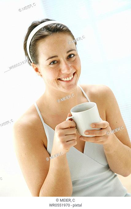 young woman holding a cup of tea in her hands and is smiling at the camera