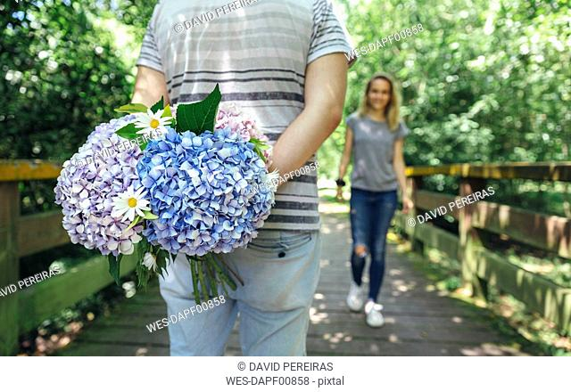 Man holding a bouquet of hydrangeas behind his back to surprise his girlfriend