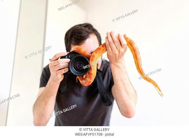 Snake slithering around camera of a man