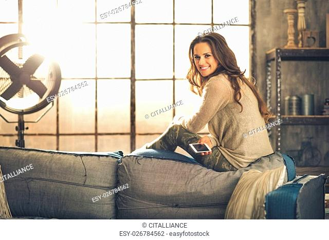 A brunette woman is smiling with phone sitting on the back of a sofa. Industrial chic ambiance and cozy atmosphere, sunlight is streaming through the loft...