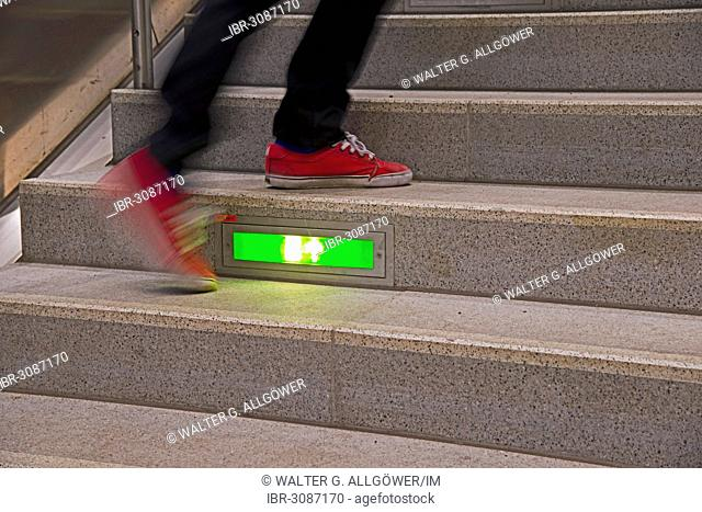 Person rushing up a public staircase with a green illuminated emergency exit sign
