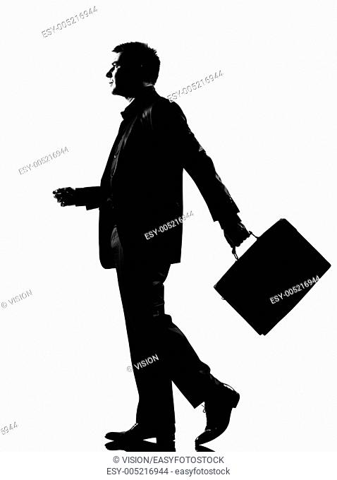 silhouette caucasian business man walking profile with briefcase full length on studio isolated white background