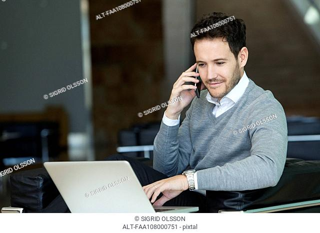 Businessman using cell phone and laptop computer at hotel lobby