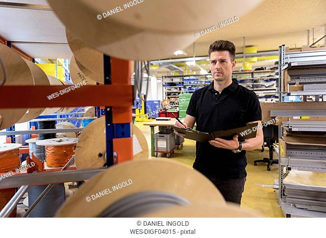 Man with clipboard in factory taking notes