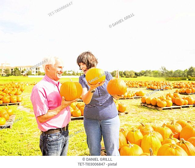 Couple talking and holding pumpkins