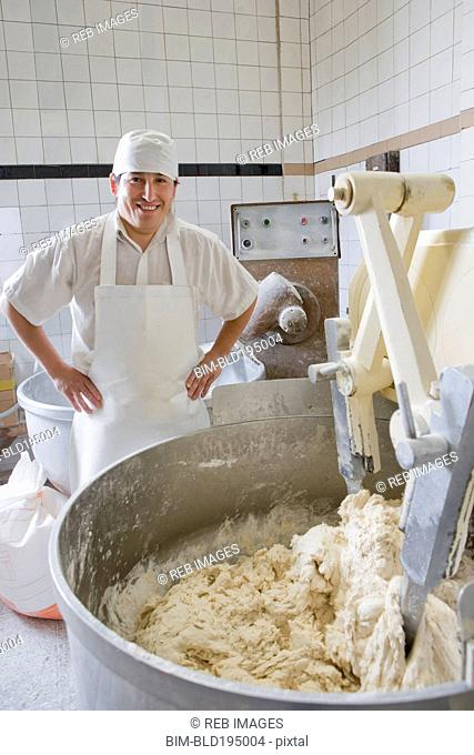 Hispanic baker mixing dough