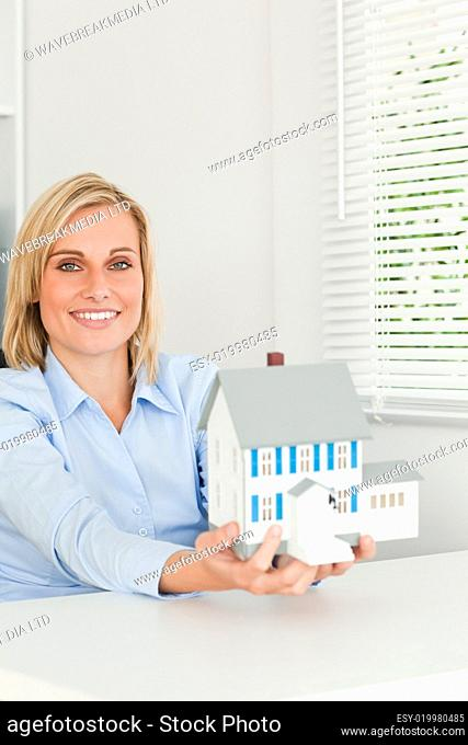 Gorgeous businesswoman showing model house looks into camera