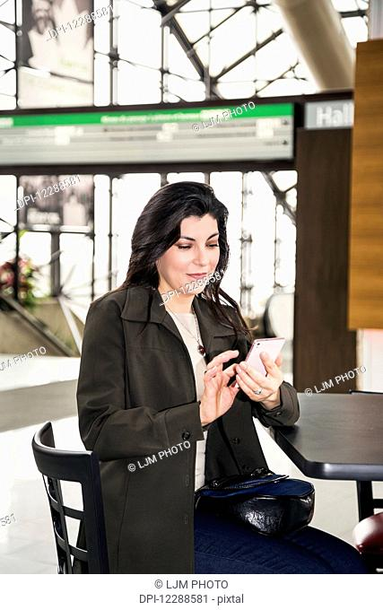 Mature business woman texting while taking a break in the atrium of an office building; Edmonton, Alberta, Canada