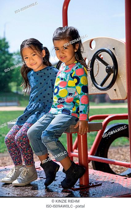 Portrait of two girls sitting on playground climbing frame