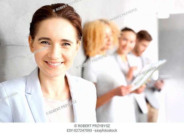 beautiful young buisinesswoman smile to colleagues.\nportrait of a young business woman smiling at colleagues