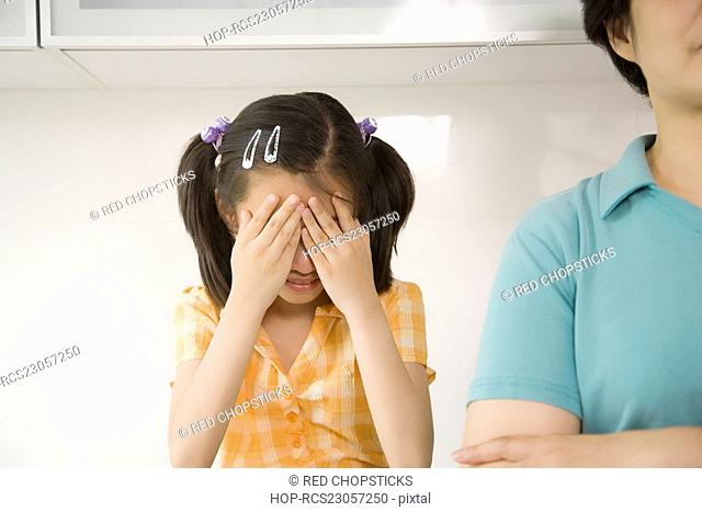 Girl hiding her face with her hands and her grandmother beside her
