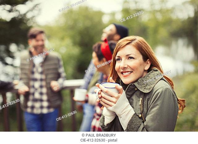 Smiling woman drinking coffee on balcony