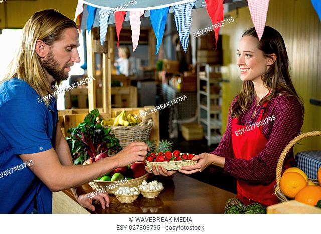 Smiling female staff offering strawberry to customer at organic section