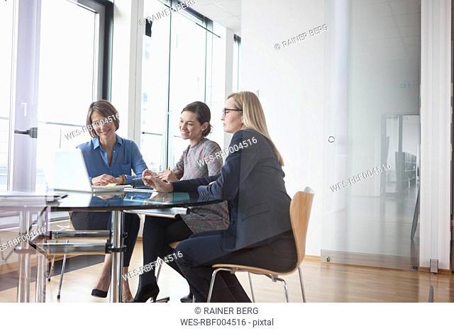 Three businesswomen looking at laptop