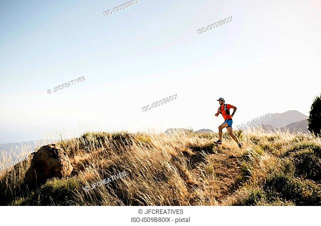 Man running outdoors in rural, hilly setting, Santa Barbara, California, USA