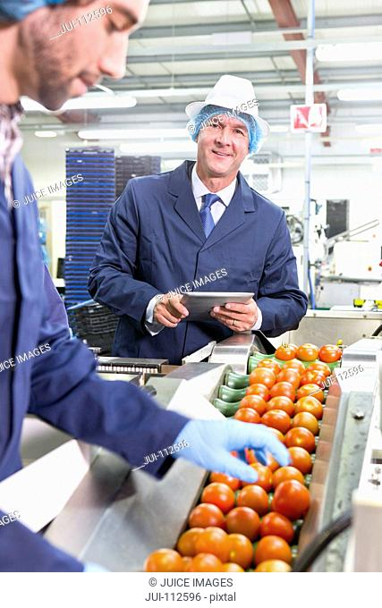 Portrait confident quality control worker with digital tablet inspecting ripe red tomatoes on production line in food processing plant