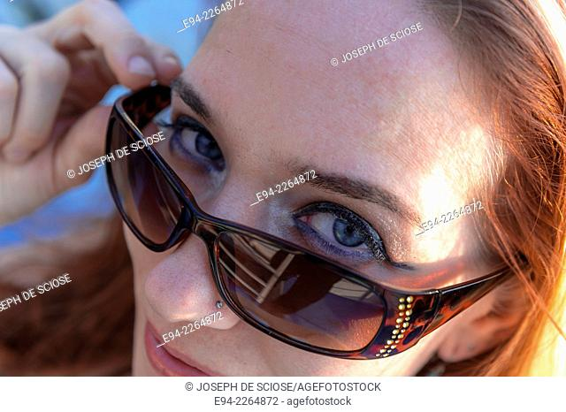 A 34 year old redheaded woman looking over her sunglasses smiling at the camera