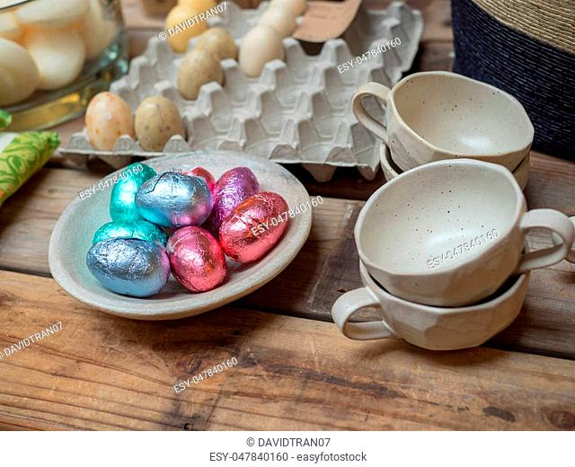 Easter eggs and real eggs on display on a wooden counter