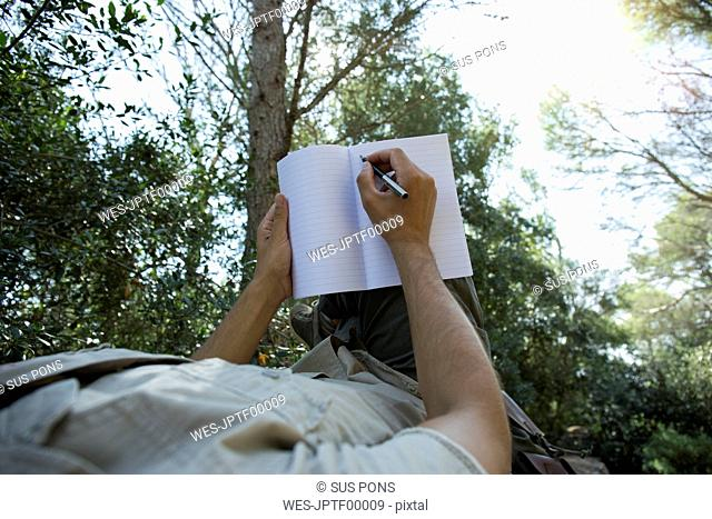 Man lying in hammock writing in notebook, partial view