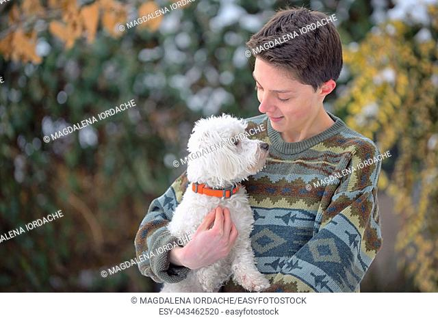Maltese dog and teen boy on winter park