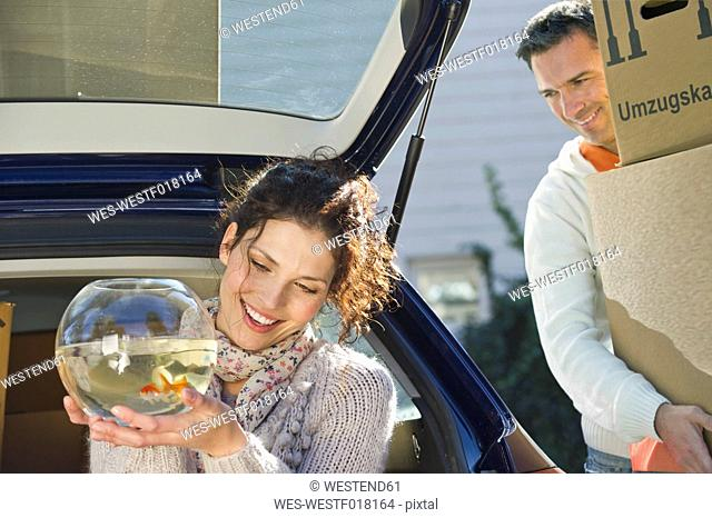 Germany, Bavaria, Grobenzell, Woman holding goldfish bowl with man in background, smiling