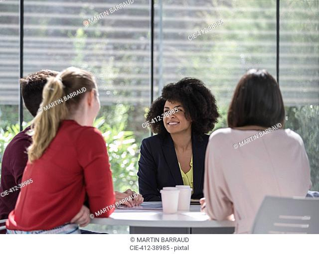 Businesswomen talking, planning at table in meeting