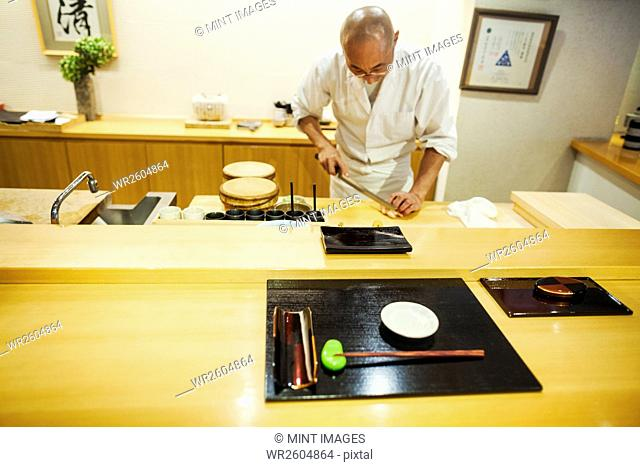 A chef working in a small commercial kitchen, an itamae or master chef grating horseradish root for wasabi