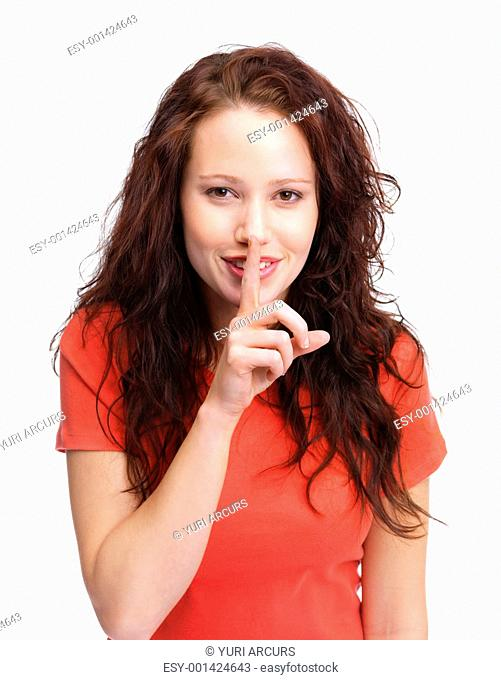 Portrait of a beautiful young female gesturing silence against white background
