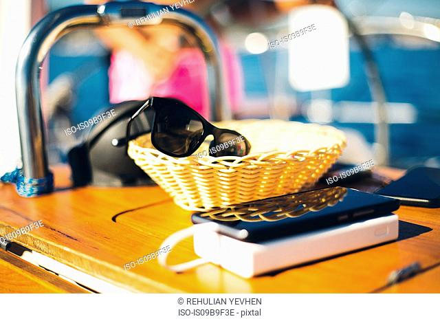 Phone beside sunglasses in a basket, boat interior