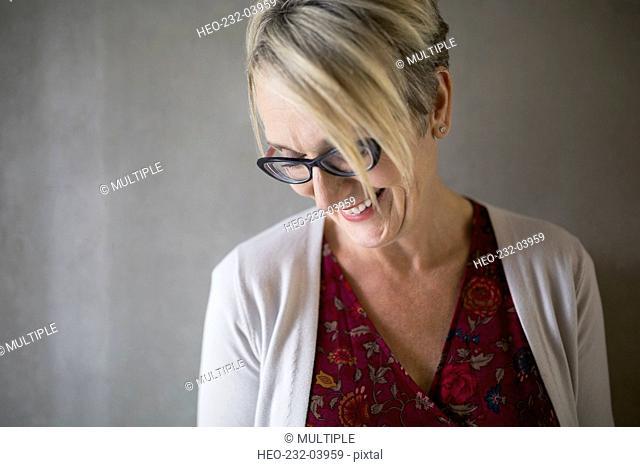 Close up portrait smiling blonde businesswoman looking down