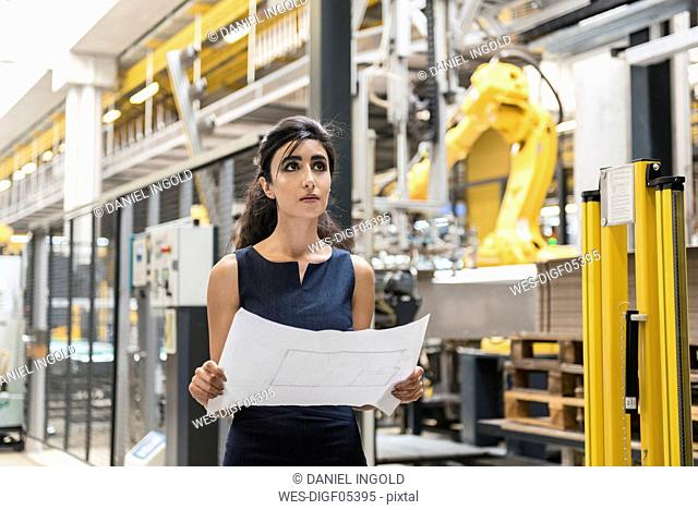 Woman holding plan in factory shop floor with industrial robot