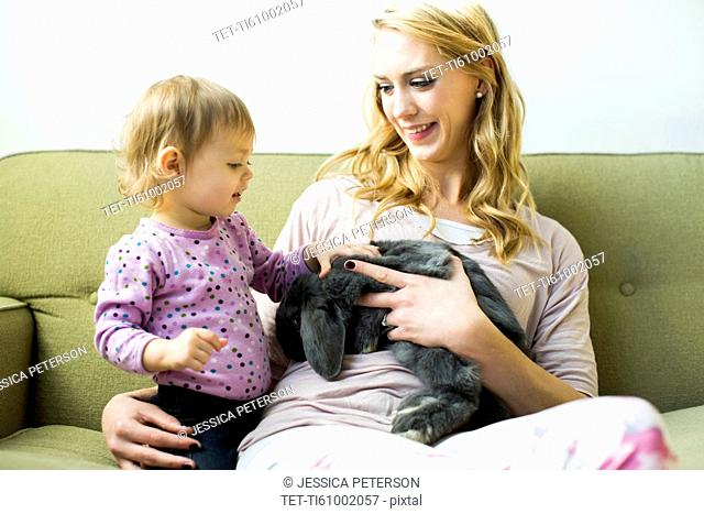 Mother and daughter (12-17 months) sitting on sofa stroking rabbit