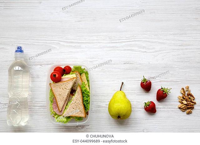 Healthy school lunch box with fresh organic vegetables sandwiches, walnuts, fruits and bottle of water on white wooden background, flat lay