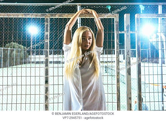 girl leaning against metal fence at night. Russian ethnicity
