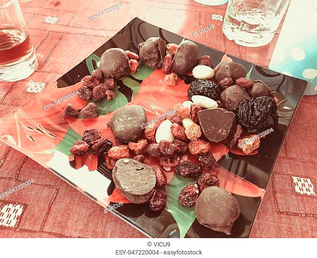 Dried fruits and chocolates on a plate. Close up shot