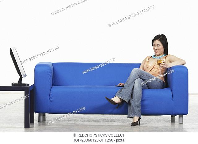 Young woman holding a glass of red wine sitting on a couch