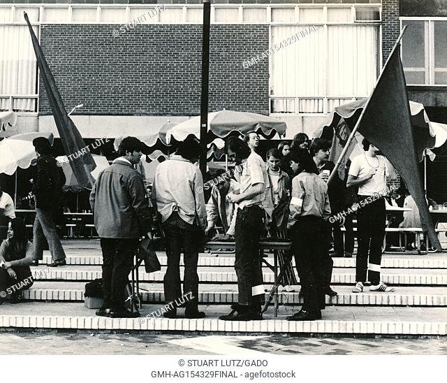 A group of students wearing hippie attire gathers on steps and prepares to raise flags during an anti Vietnam War student sit-in protest at North Carolina State...